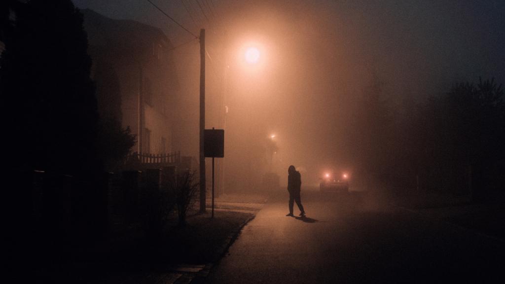 skryta w mroku ulica oświetlona jedną latarnią pod którą stoi niewyraźna postać
