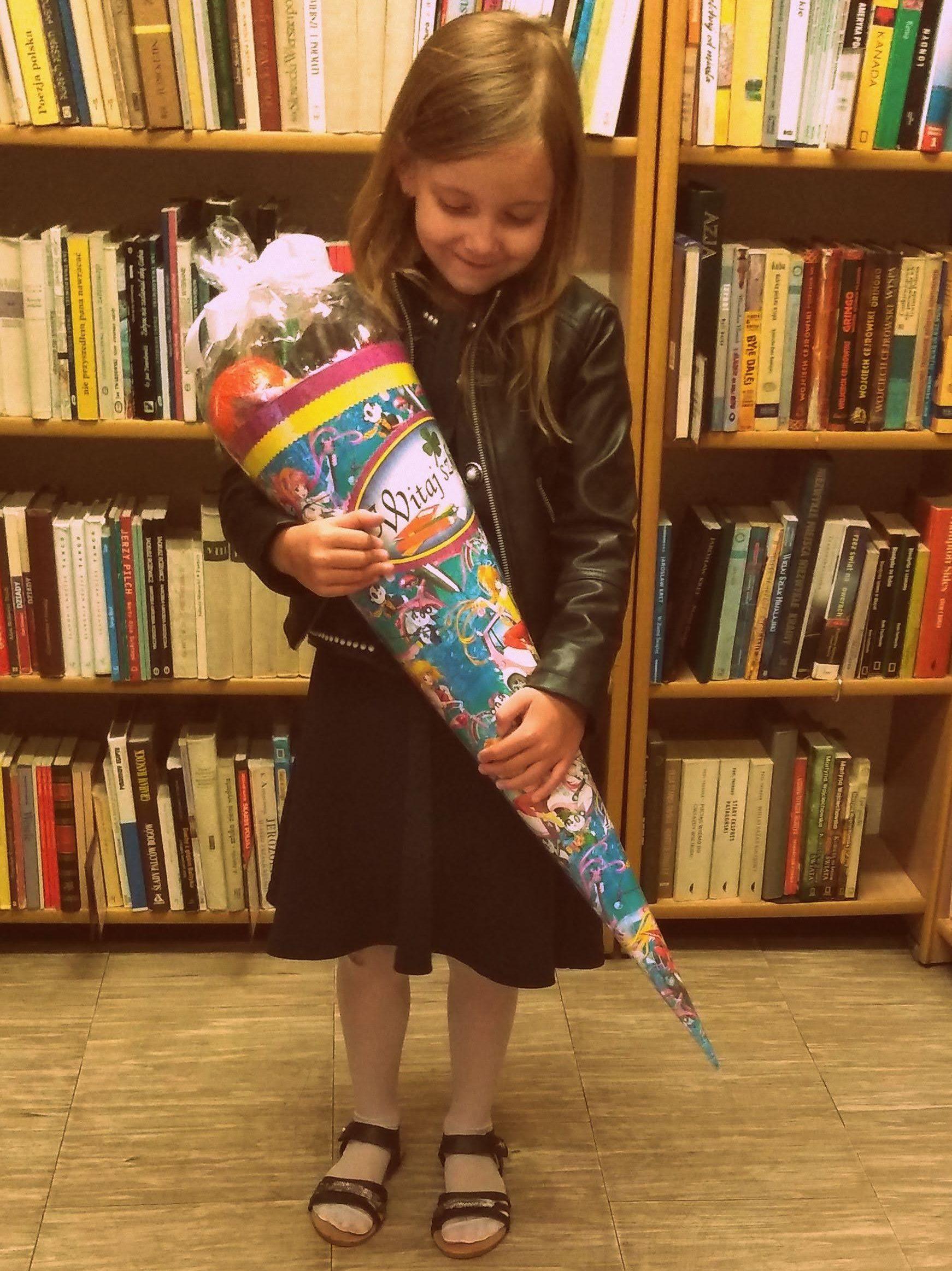 dziewczyna w czarnej sukience trzymająca kolorową tytę na tle półek z książkami