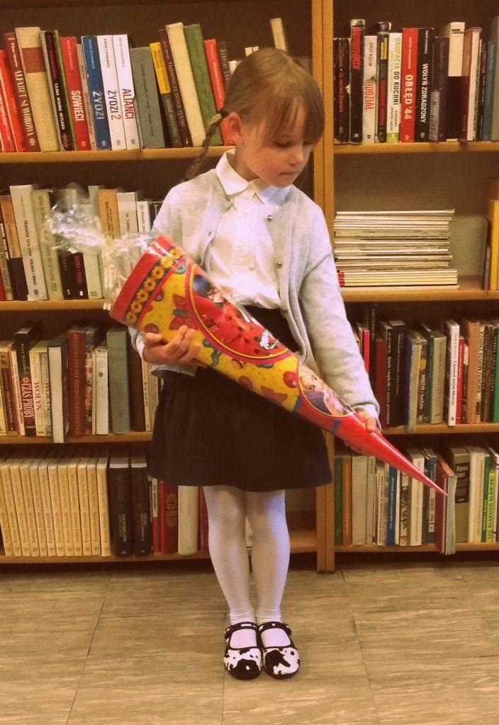 dziewczynka ubrana na biało-czarno trzymająca tytę na tle półek z książkami